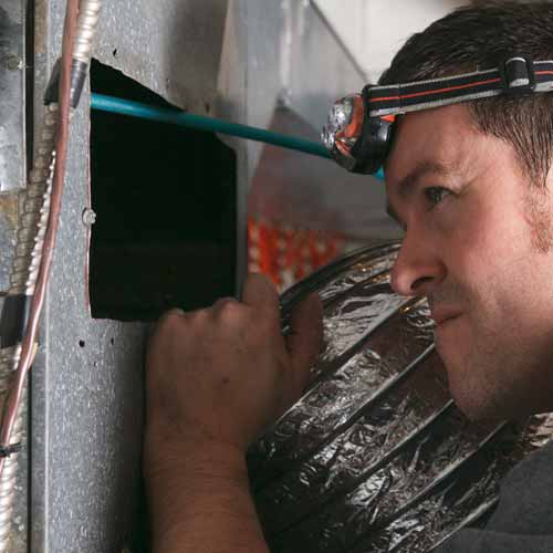 Air duct cleaning specialist doing a visual inspection of furnace ducts